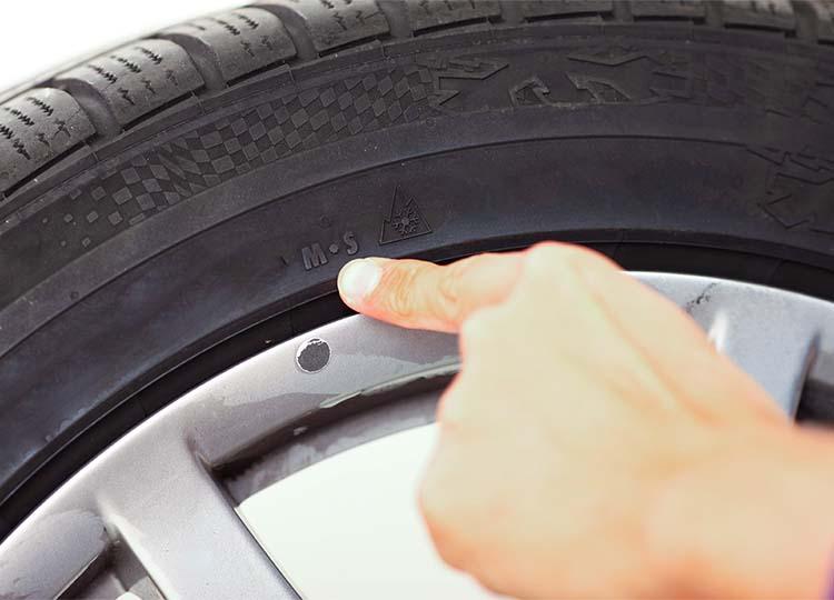 Gros plan sur la main d'un mécanicien pointant du doigt les logo M+S et 3PMSF désignant un pneumatique adapté pour les conditions hivernales.